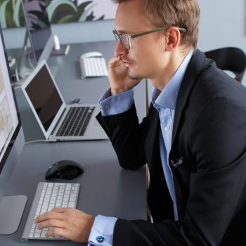 Handsome young business man working with computer in office.
